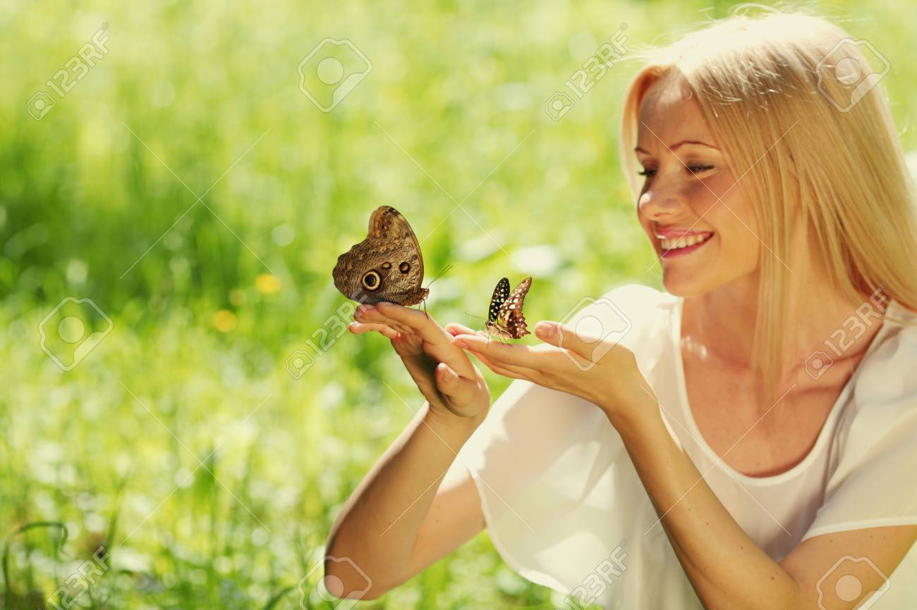 Woman playing with a butterfly on green grass Stock Photo - 11950521