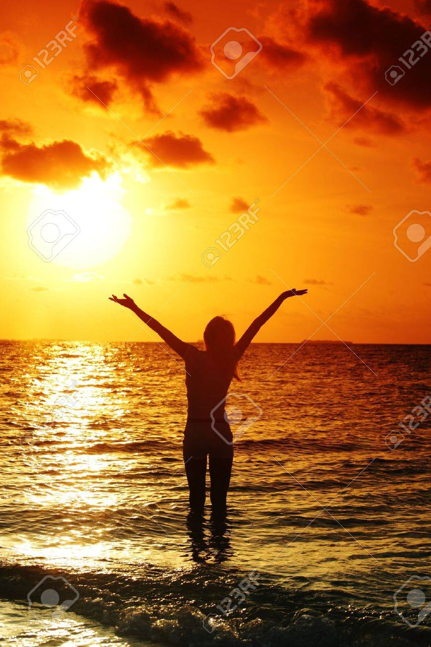 happy woman standing on a sunset in ocean waves - 11975139