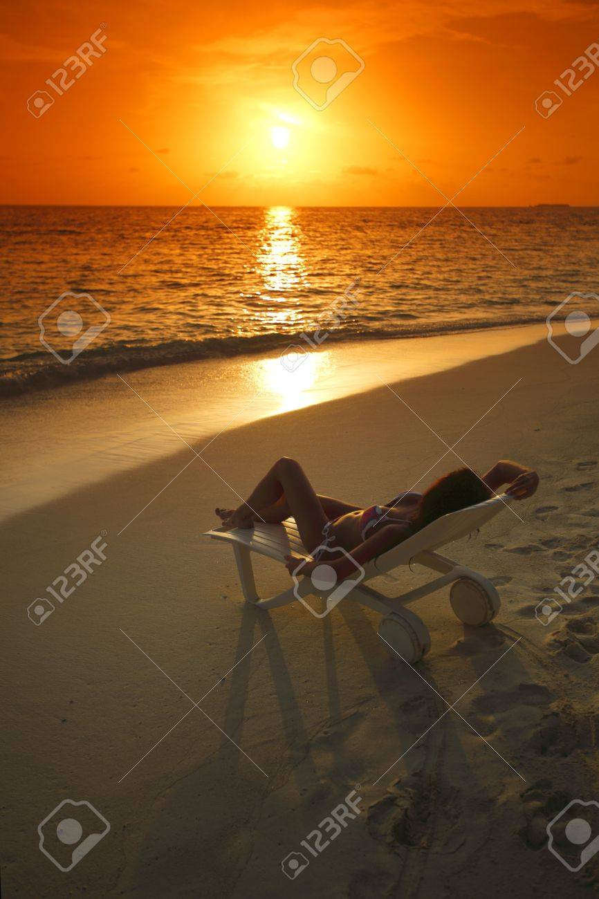 Woman in chaise-lounge relaxing on sunset beach Stock Photo - 15982546