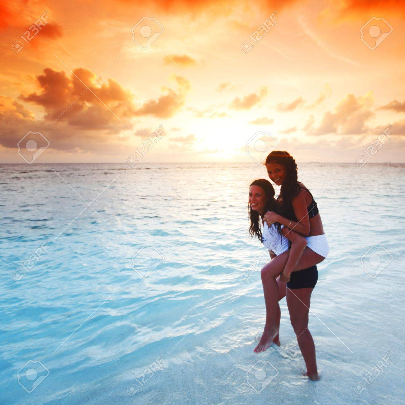 Two happy wimen playing in water on sunset Stock Photo - 15992408
