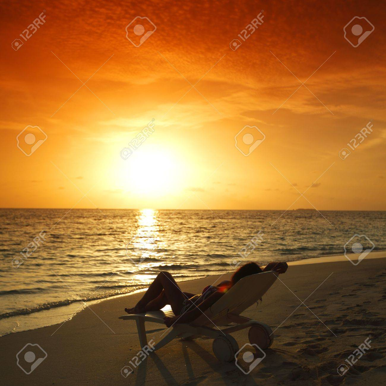 Beach sunset with chairs - Woman In Chaise Lounge Relaxing On Sunset Beach Stock Photo 16339022