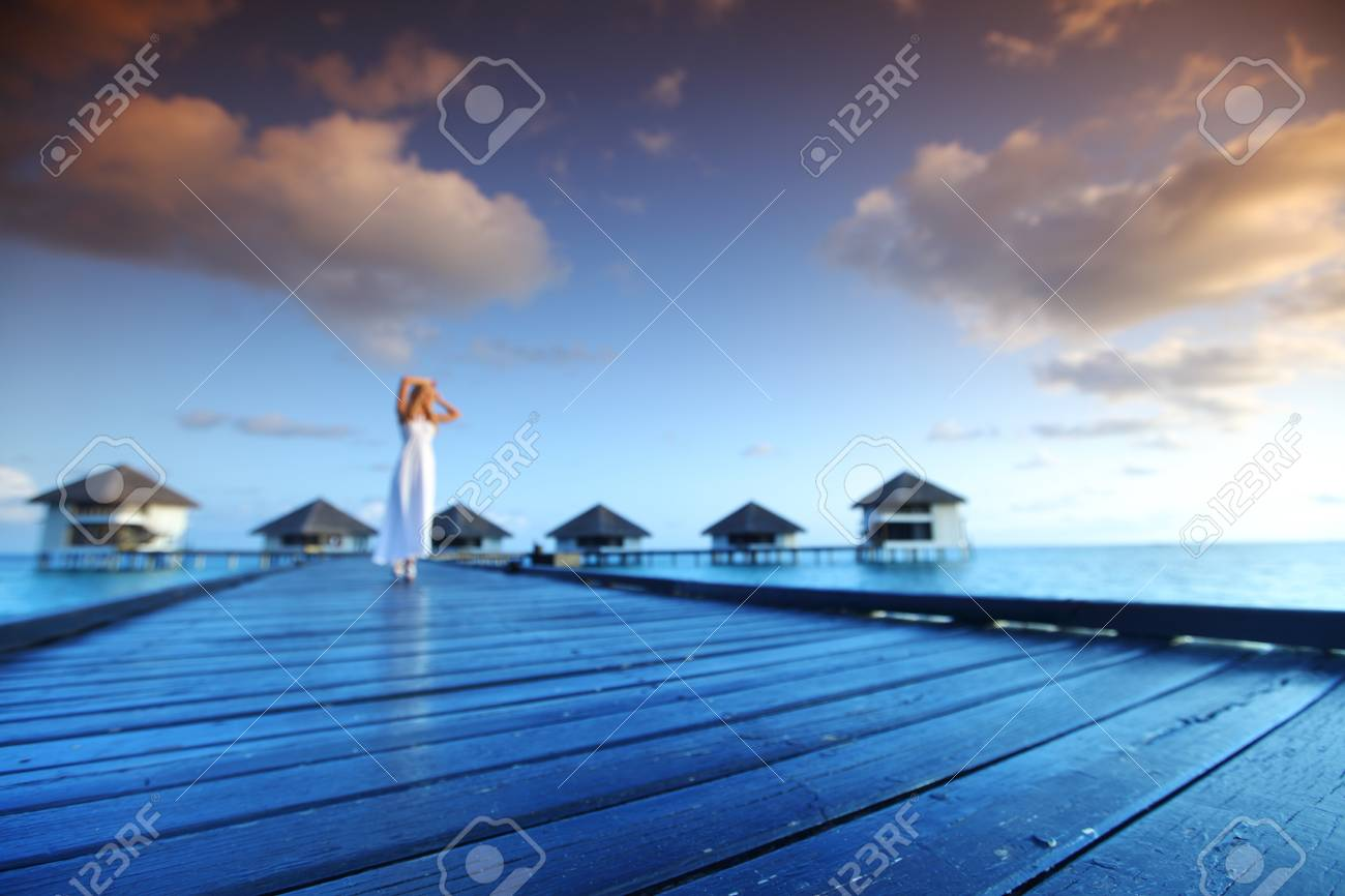 woman in a dress on a bridge home sea and the maldivian sunset on the background Stock Photo - 16536710