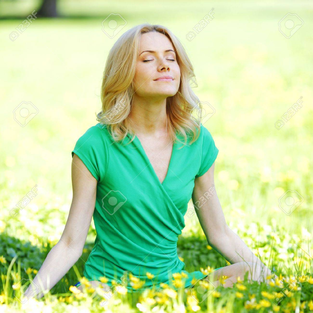 Beautiful young woman sitting on flower field in lotus pose Stock Photo - 19761840