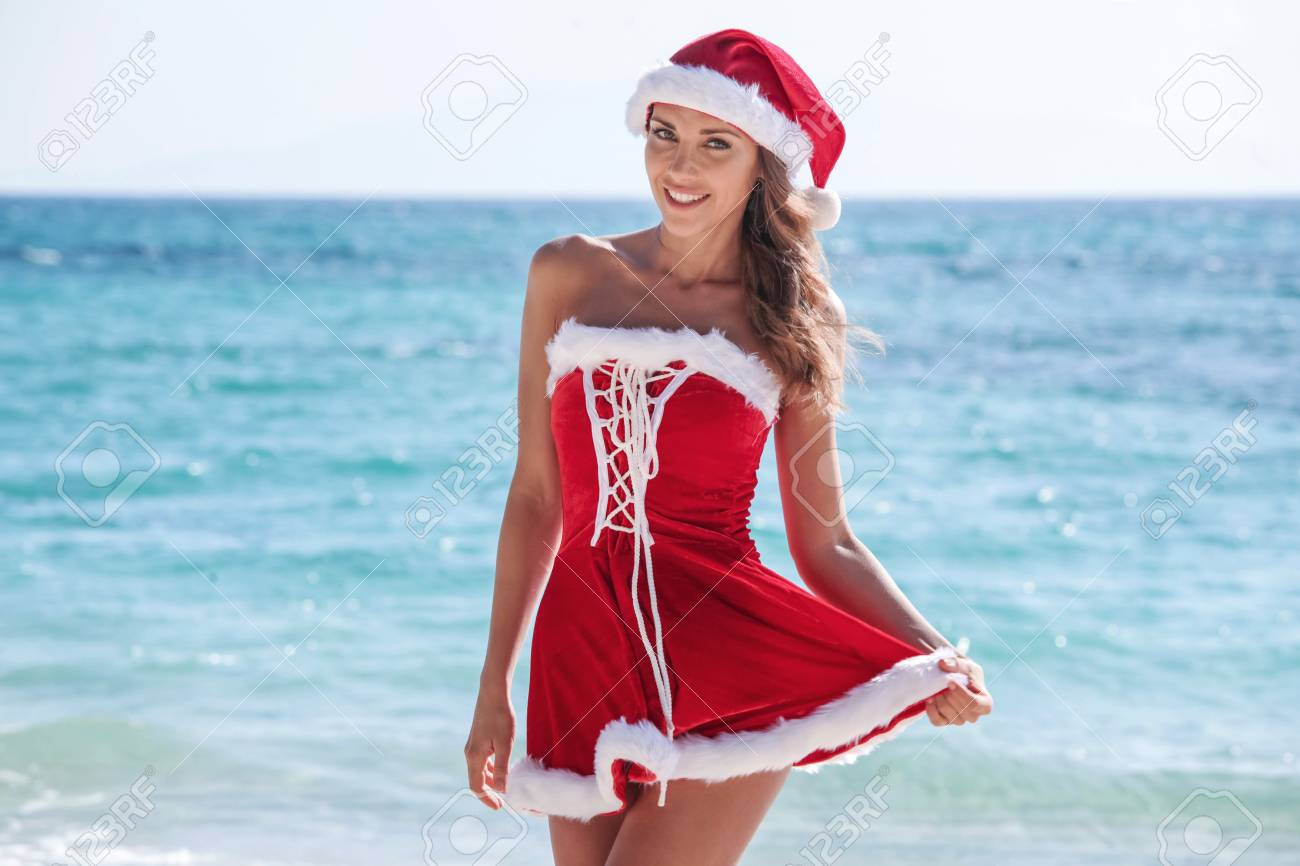 Model In Christmas Vacation.Beautiful Woman In Mrs Claus Custume On Tropical Beach Christmas