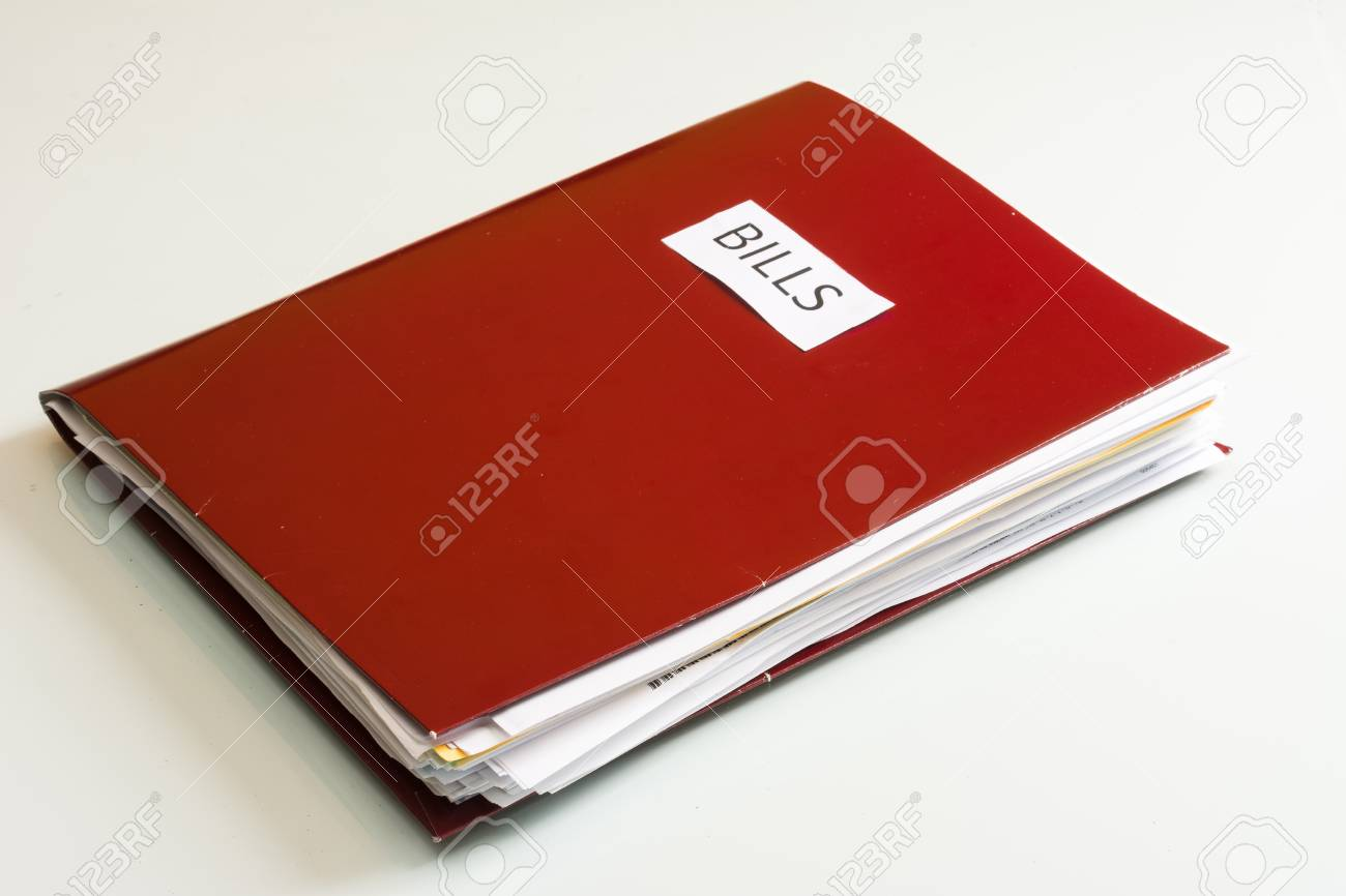 Folder full of business papers  bills, accounts receivable,invoices,receipts,etc  Blue folder with a business paperwork and red tape Stock Photo - 22118098
