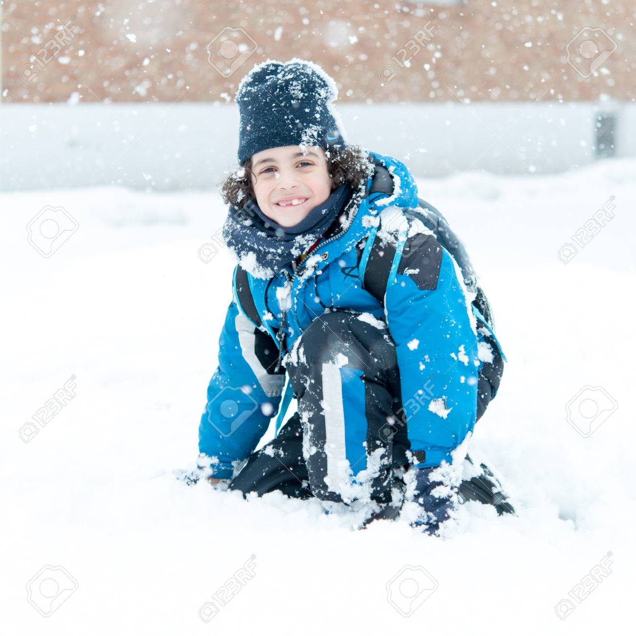 Boy Sitting In Snow And Enjoying The Canadian Winter. He Is ...