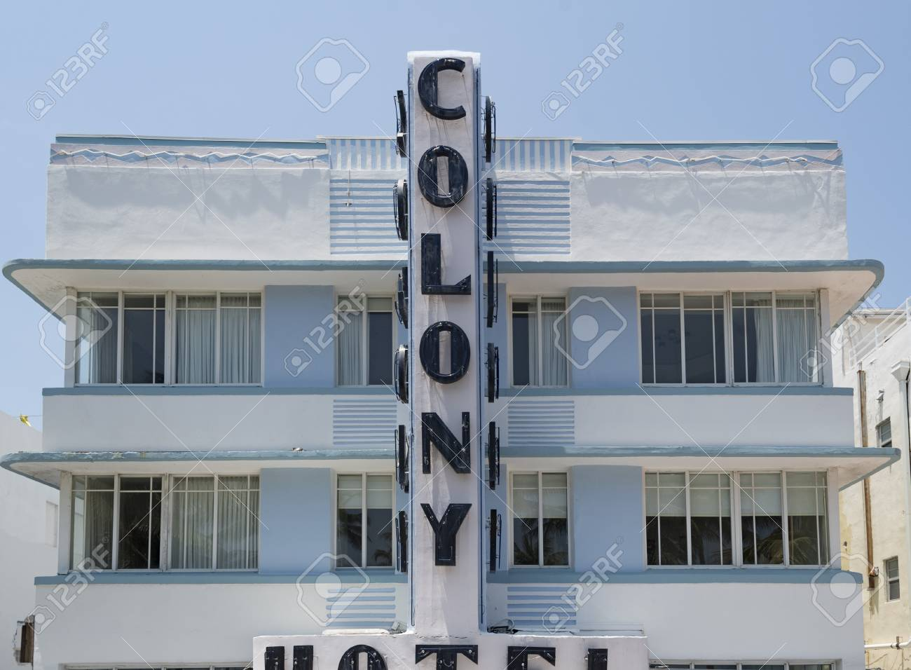 colony hotel facade pastel colored art deco building in daytime the