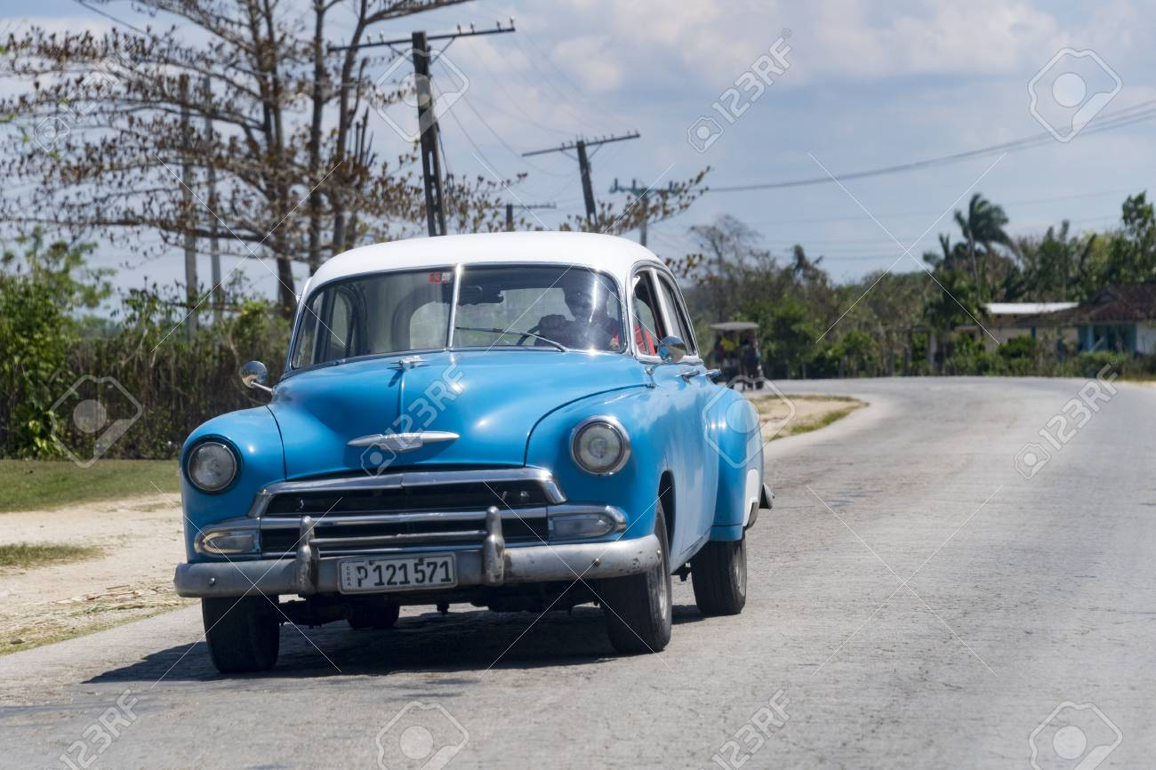 Cuban transportation: Blue old Chevrolet driving in a rural road