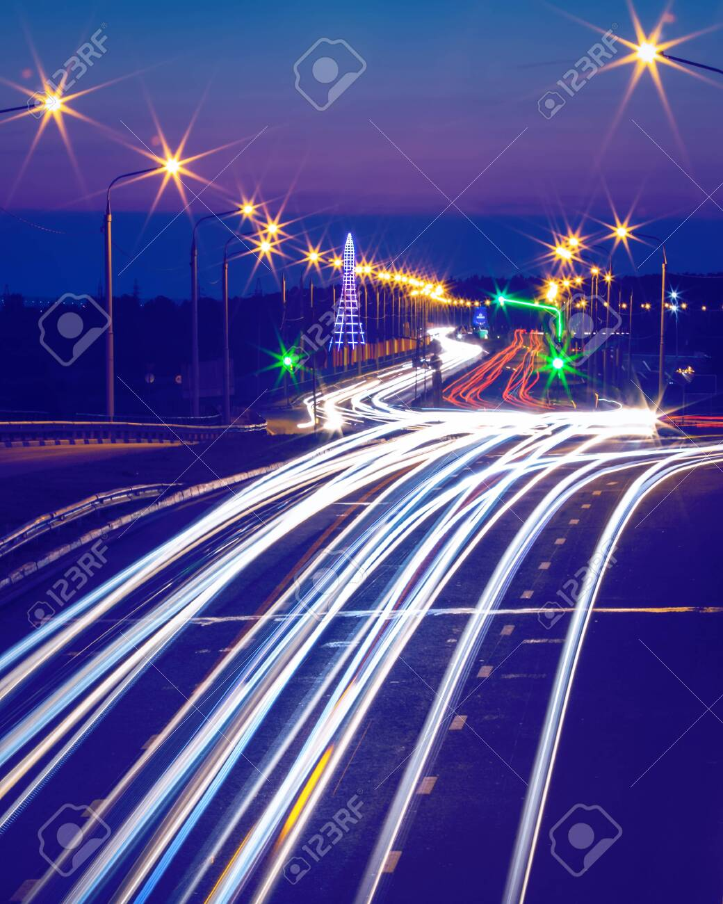 Traces of headlights from cars moving at night on the bridge, illuminated by lanterns. Abstract city landscape with highway at dusk. - 154893188