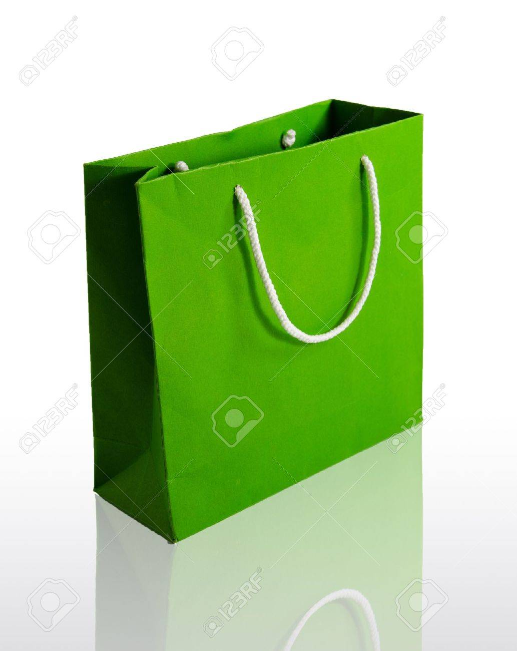 Green paper bag on reflect floor and white background - 11133177