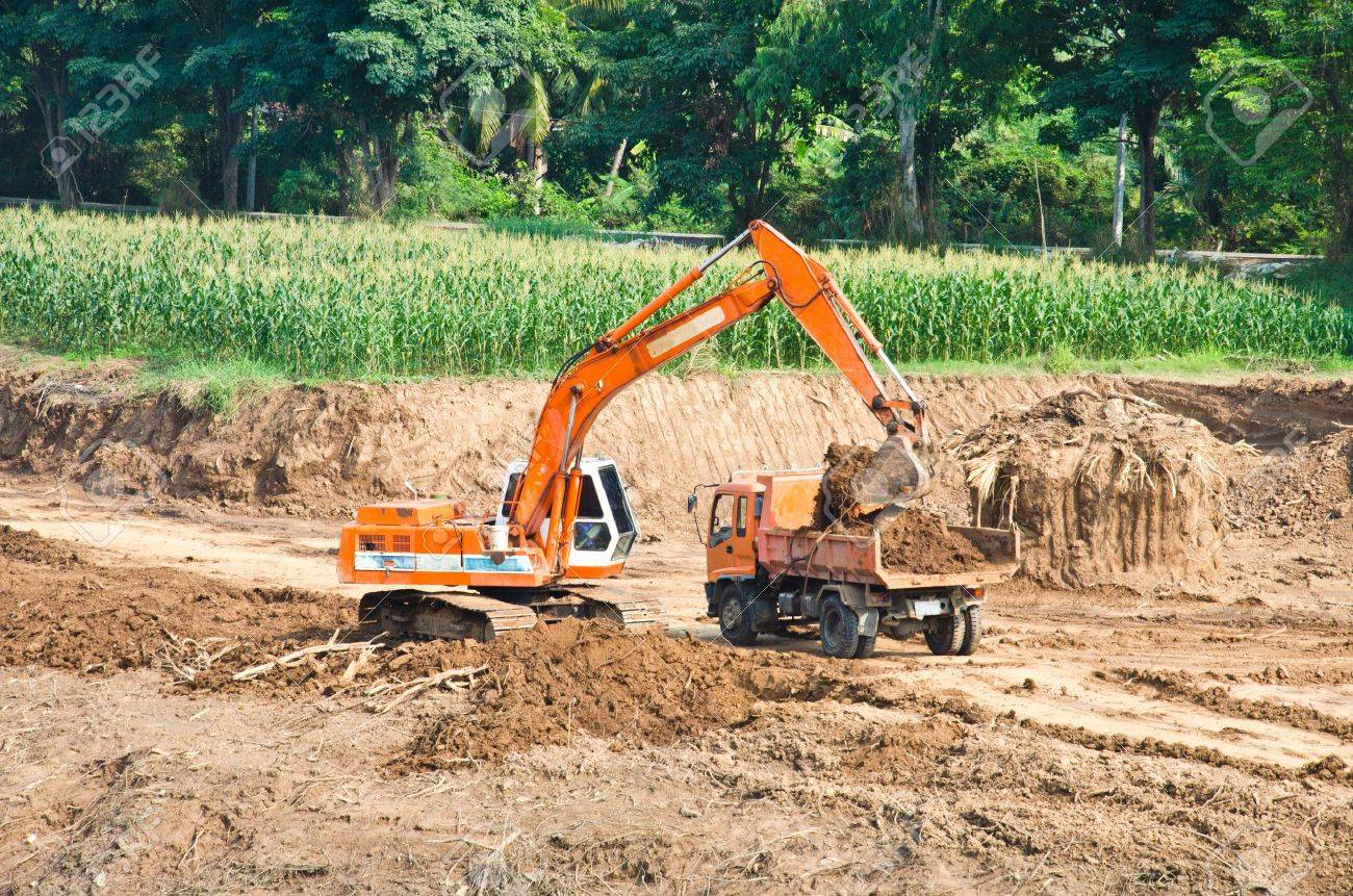 Heavy excavator loader at soil moving works at construction site - 12308309