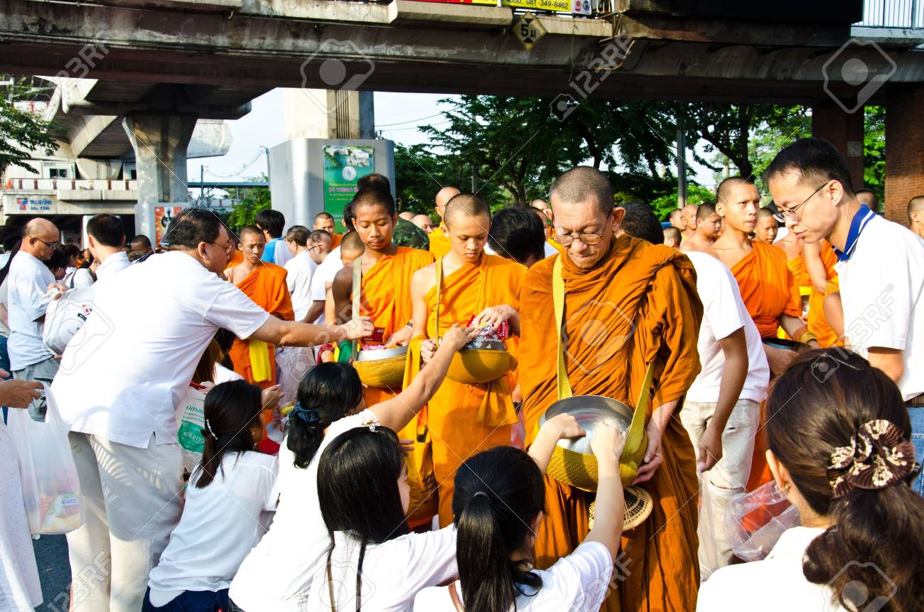 BANGKOK , THAILAND - MARCH 17: People Gives food offerings to a Buddhist monk on March 17, 2012 in Bangkok, Thailand. Thai traditional, people will make merit making by give food to monk - 12716992
