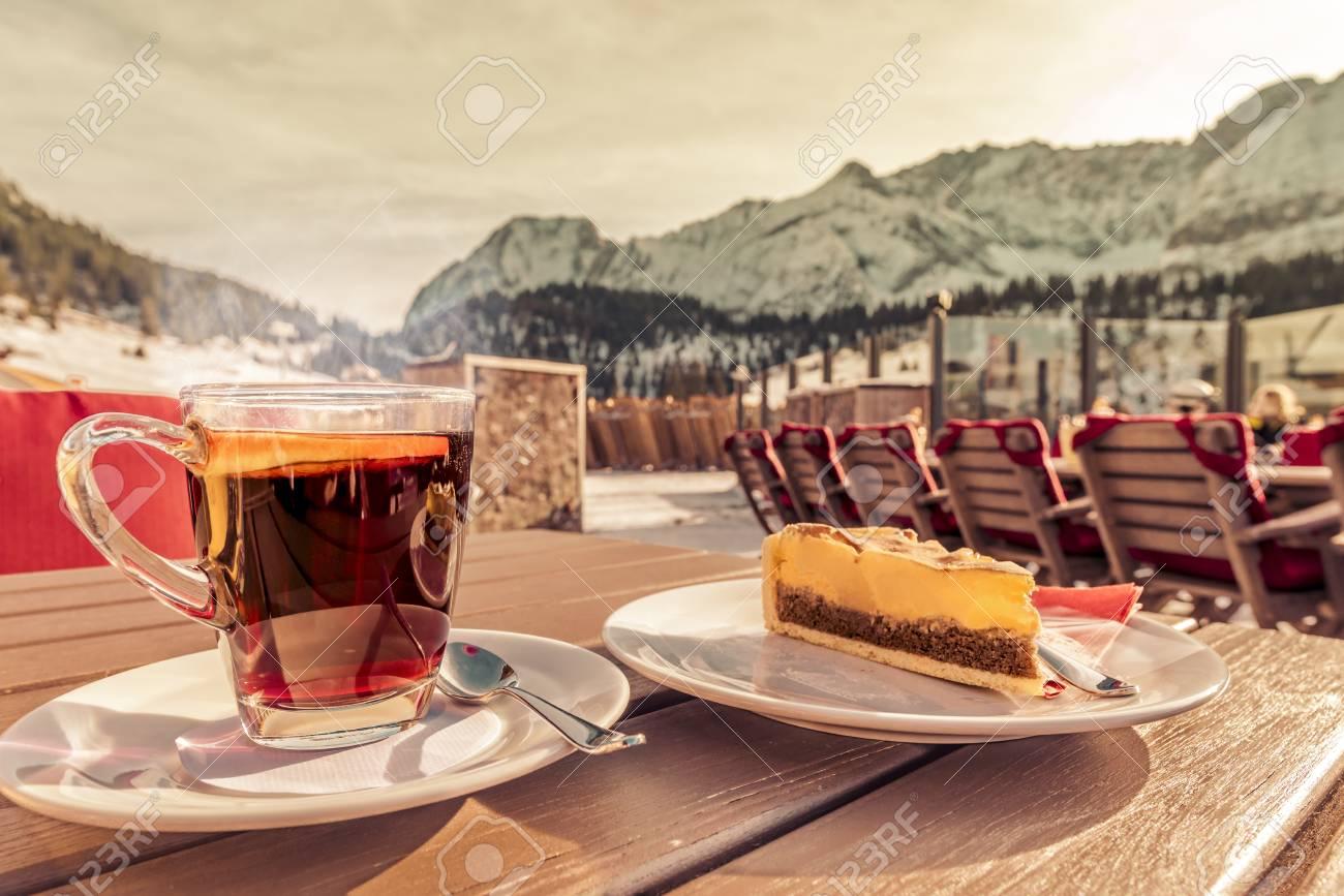 ein paar Tage entfernt zu Füßen bei Qualität Bevanda calda e torta in una località di montagna Immagine di una tazza  calda di tè, con una fetta di arancia e una deliziosa torta servita in un  ...