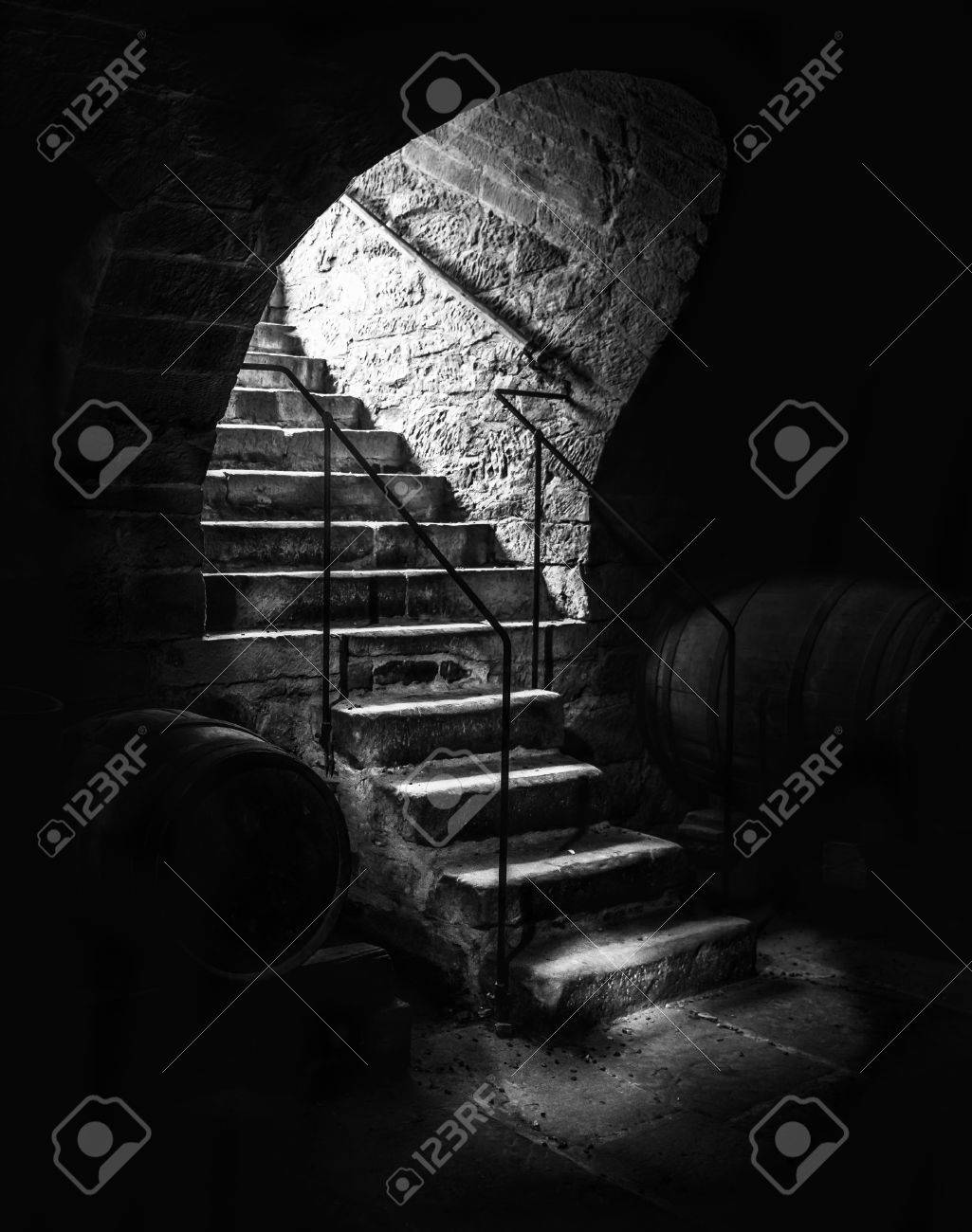 Old cellar staircase in low light dramatic black and white image with aged stone stairs