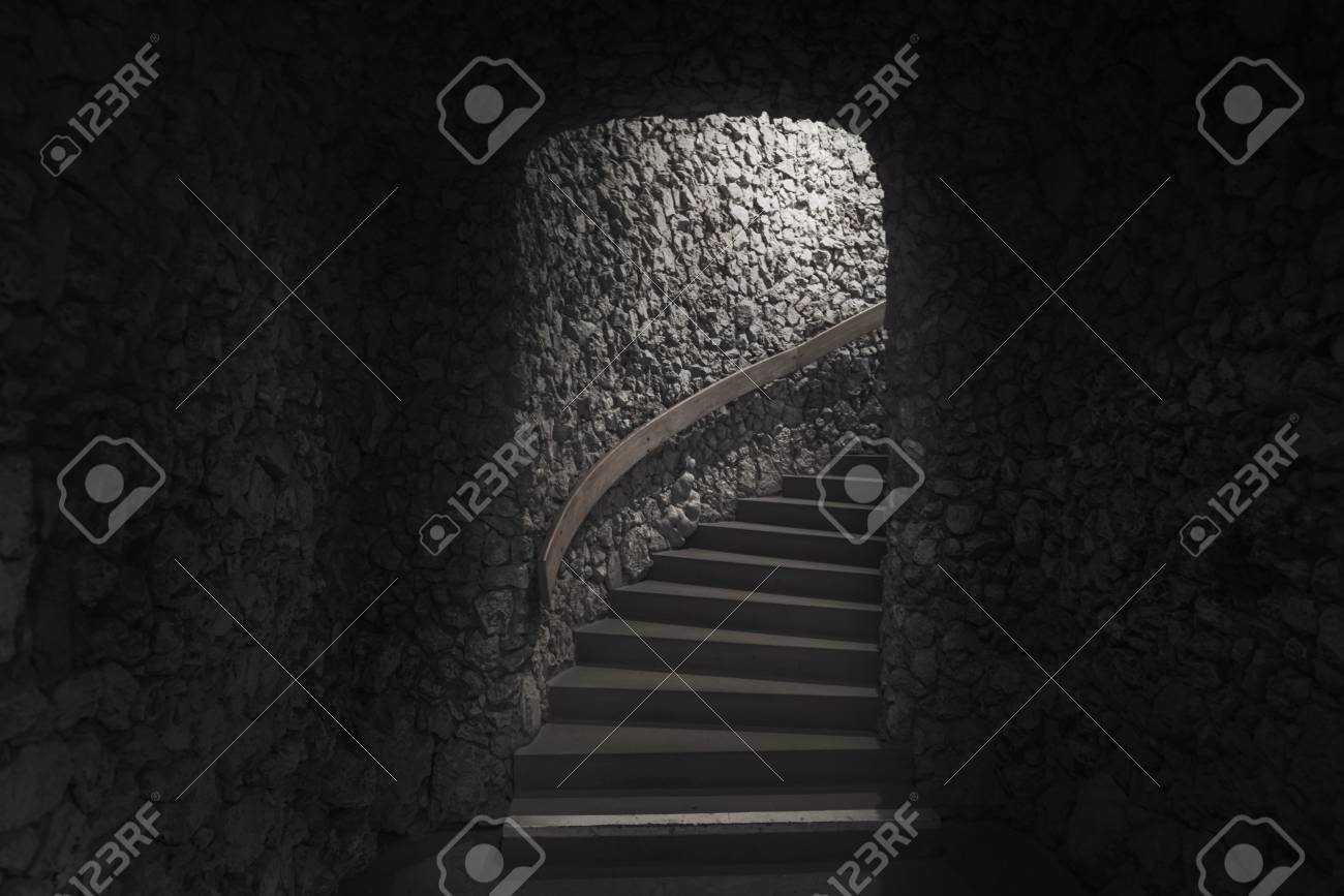 Old Dark Cellar Made From Small Pieces Of Stone And Staircase Towards The Exit And Light