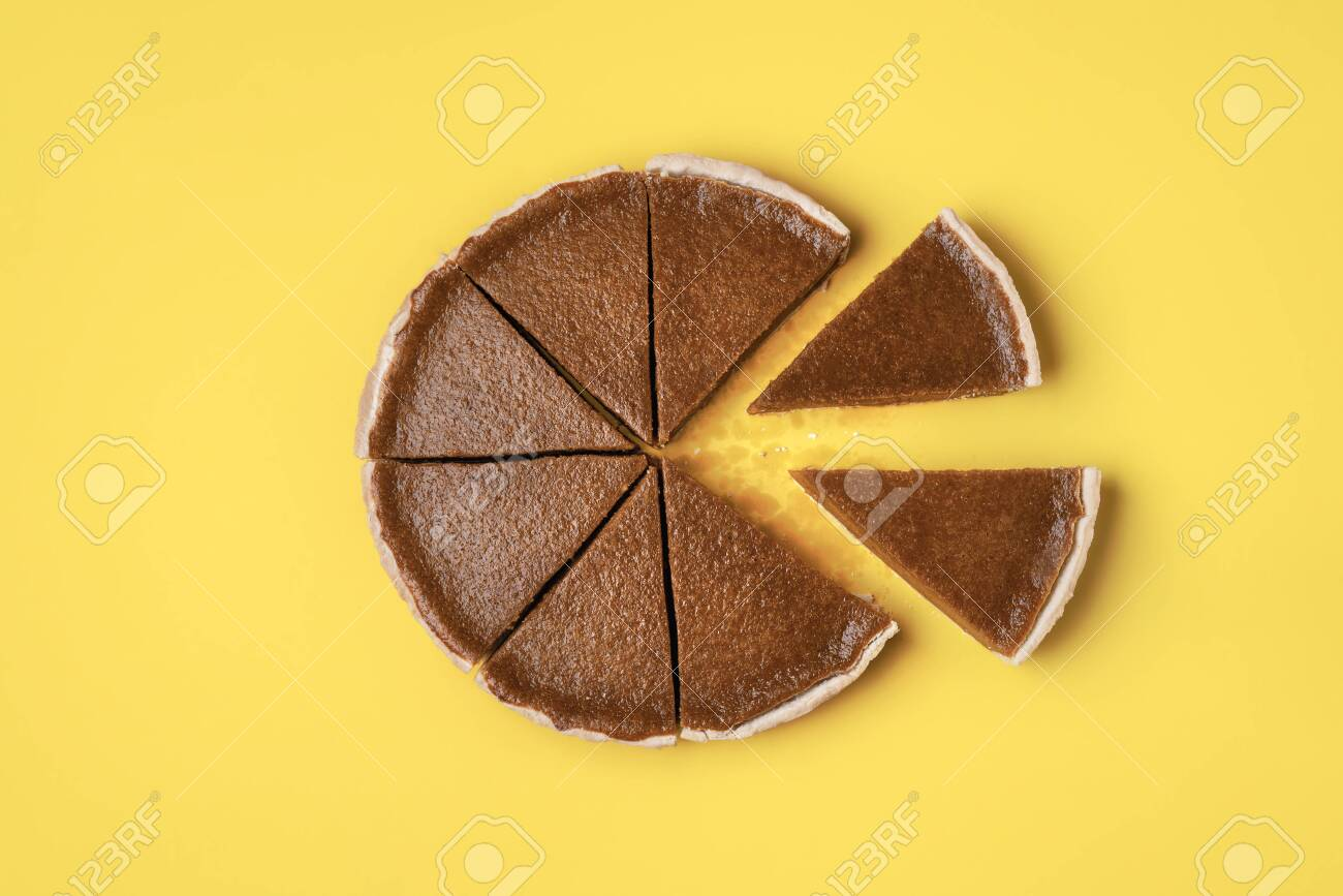 Pie slices separated from the whole pumpkin pie on a yellow background. Flat lay of traditional American pie. Minimal Thanksgiving food. Sweet pastry - 128391485