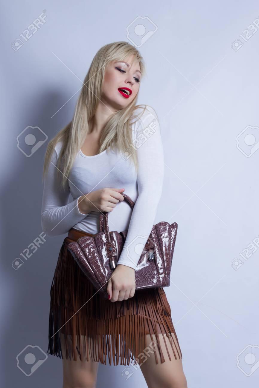 072e759aa1af Archivio Fotografico - Ritratto di affari di bella giovane donna bionda su  una priorità bassa bianca. La ragazza indossa una gonna di pelle marrone  con una ...