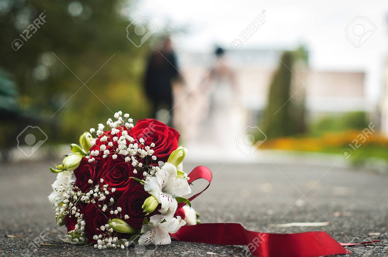 Red White Wedding Bouquet Lies On The Floor Background Stock Photo