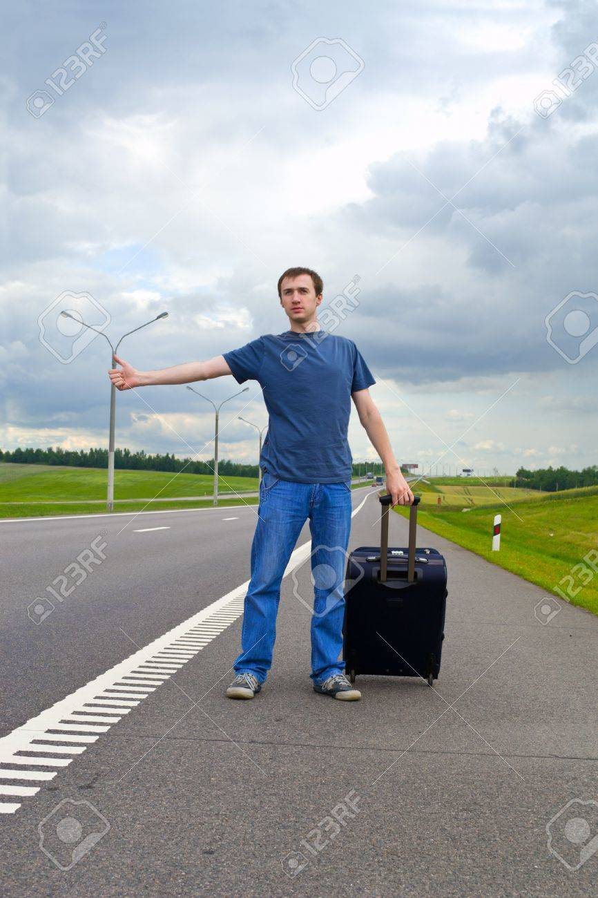 The young man pending on road with a suitcase Stock Photo - 9954674