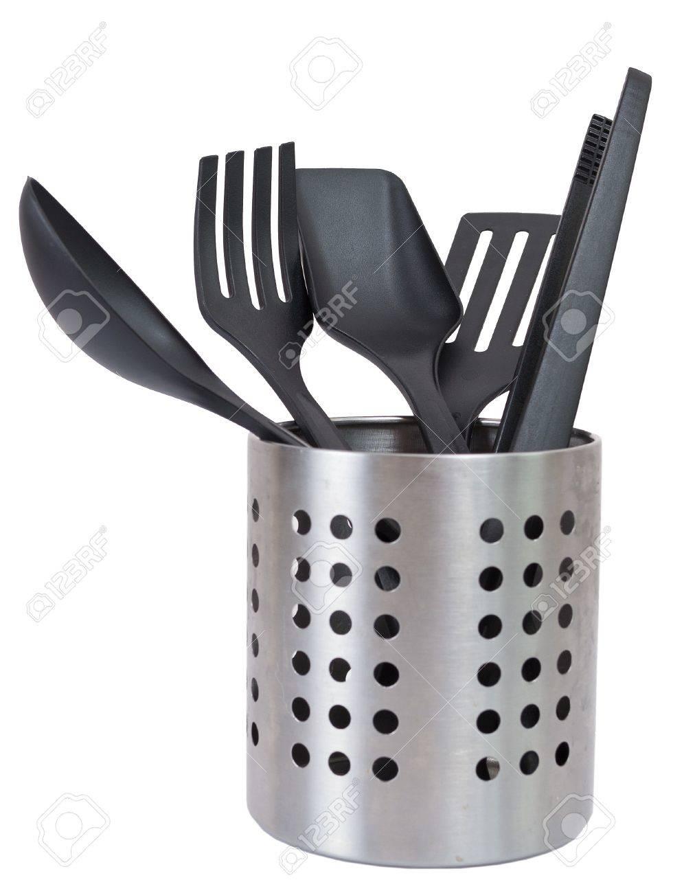 Kitchen utensils in a utensil holder isolated against a white..