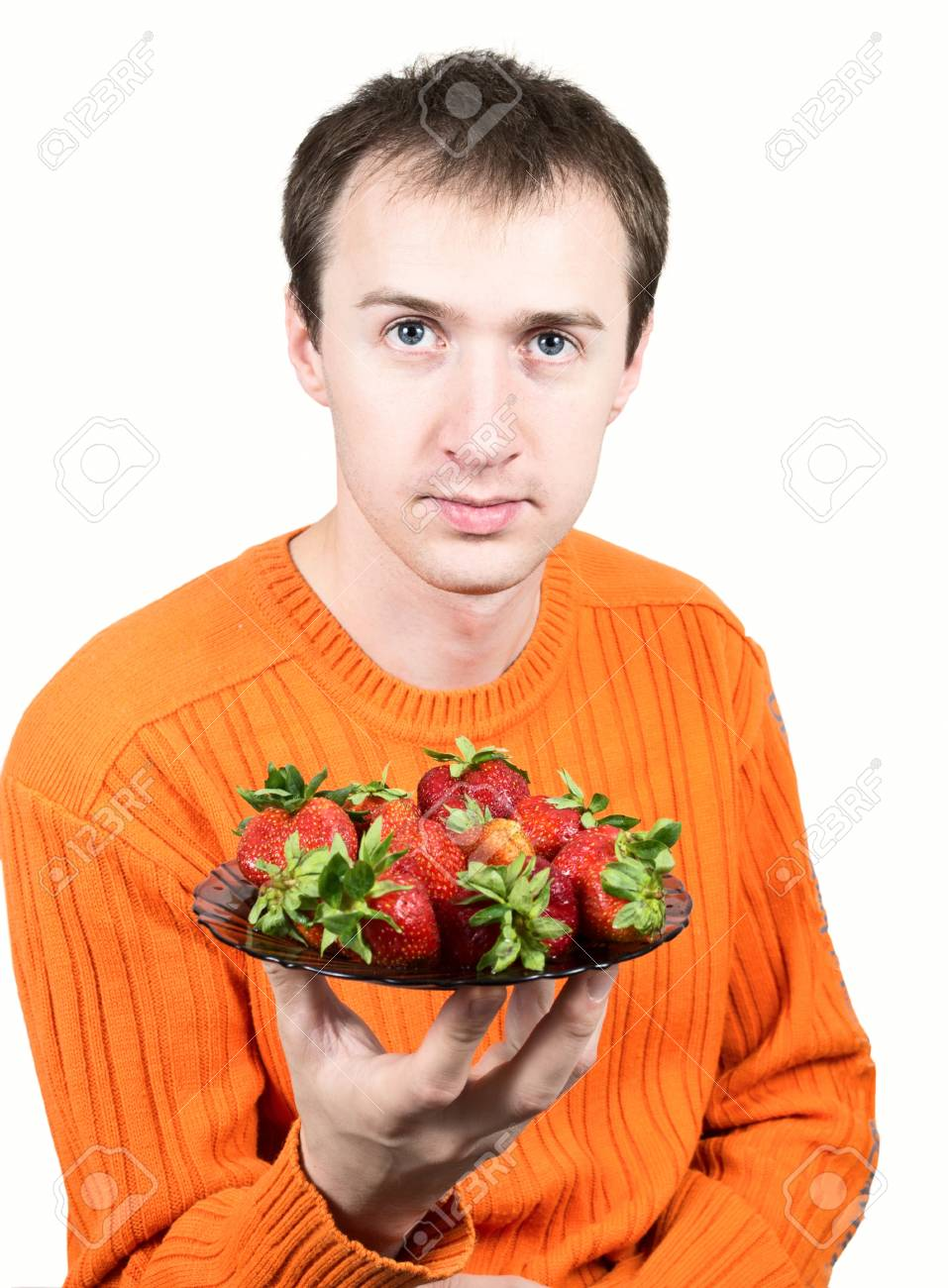Young man holding a strawberry isolated on white background. Stock Photo - 12833466