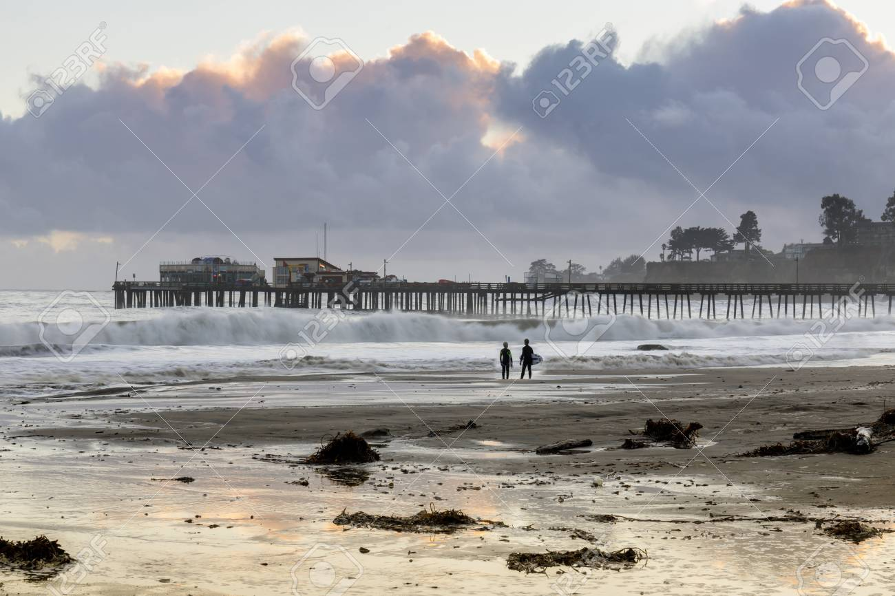 Capitola Beach and wharf in stormy clouds sunset and surfers silhouette. Capitola, Santa Cruz County, California, USA. - 112855030