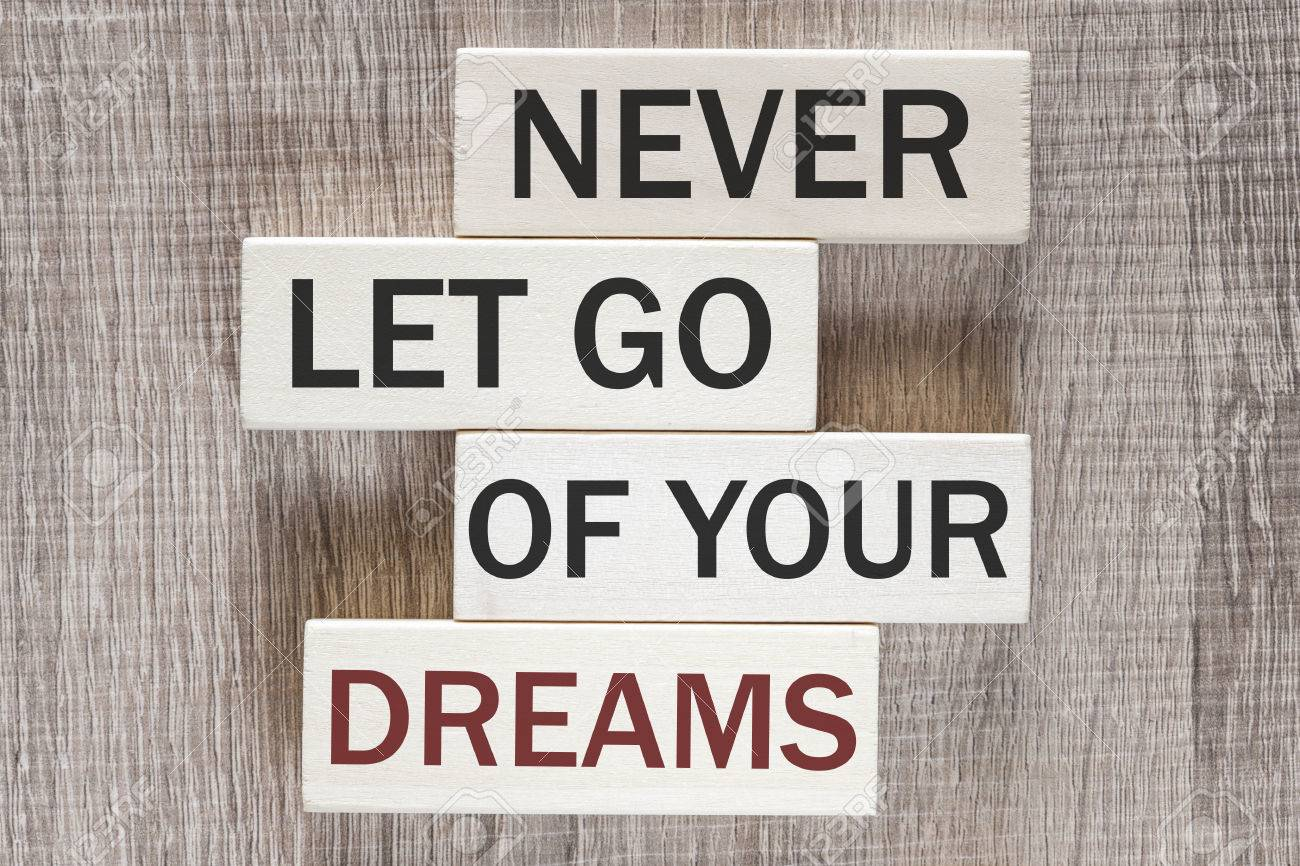 Never Let Go Of Your Dreams Motivational Quote Written On Wooden