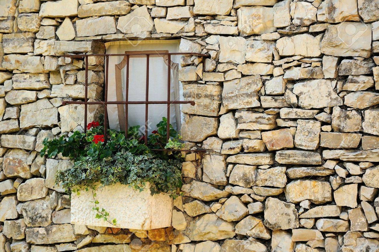 Des fenêtres d'hier et d'aujourd'hui. - Page 38 16026936-Mur-de-pierre-de-cru-avec-petite-fen-tre-et-fleurs-Banque-d'images