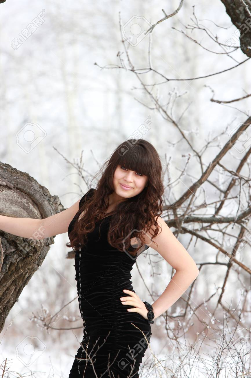 A smiling girl in a black dress near a tree in the forest Stock Photo - 19145211