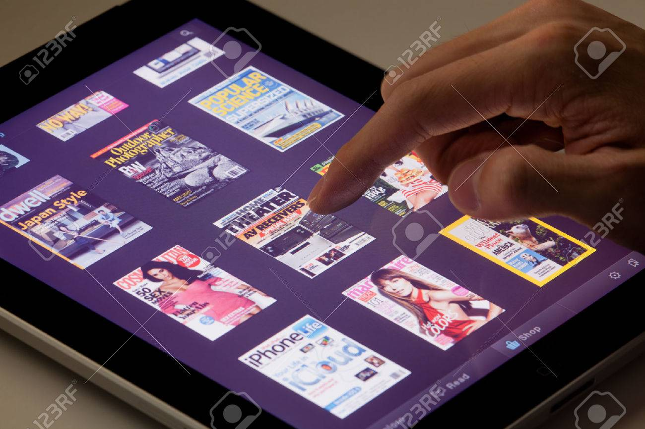 Hong Kong, China - August 7, 2011: Reading magazines on an iPad running the Zinio app. Zinio is a publishing technology and services company, which provides sales and distribution of printed material in digital format. - 42179355