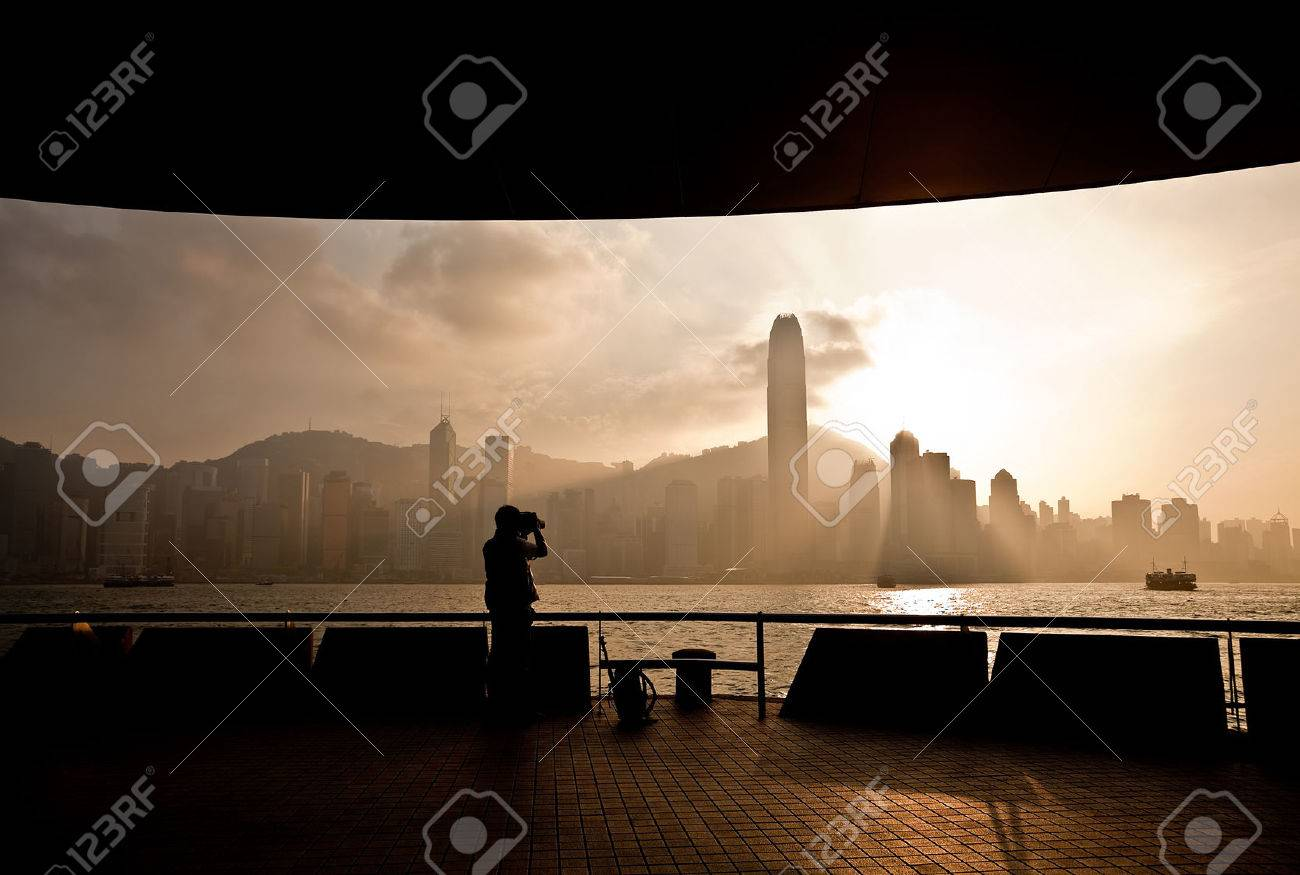 Victoria Harbor in Hong Kong at sunset with silhouette of a photographer - 44185183