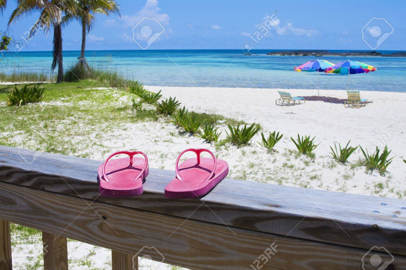 Pink Flip flops on the deck of a Caribbean beach resort. Beach umbrellas, palm trees, white sand and aqua-blue waters in the background Stock Photo - 5194496