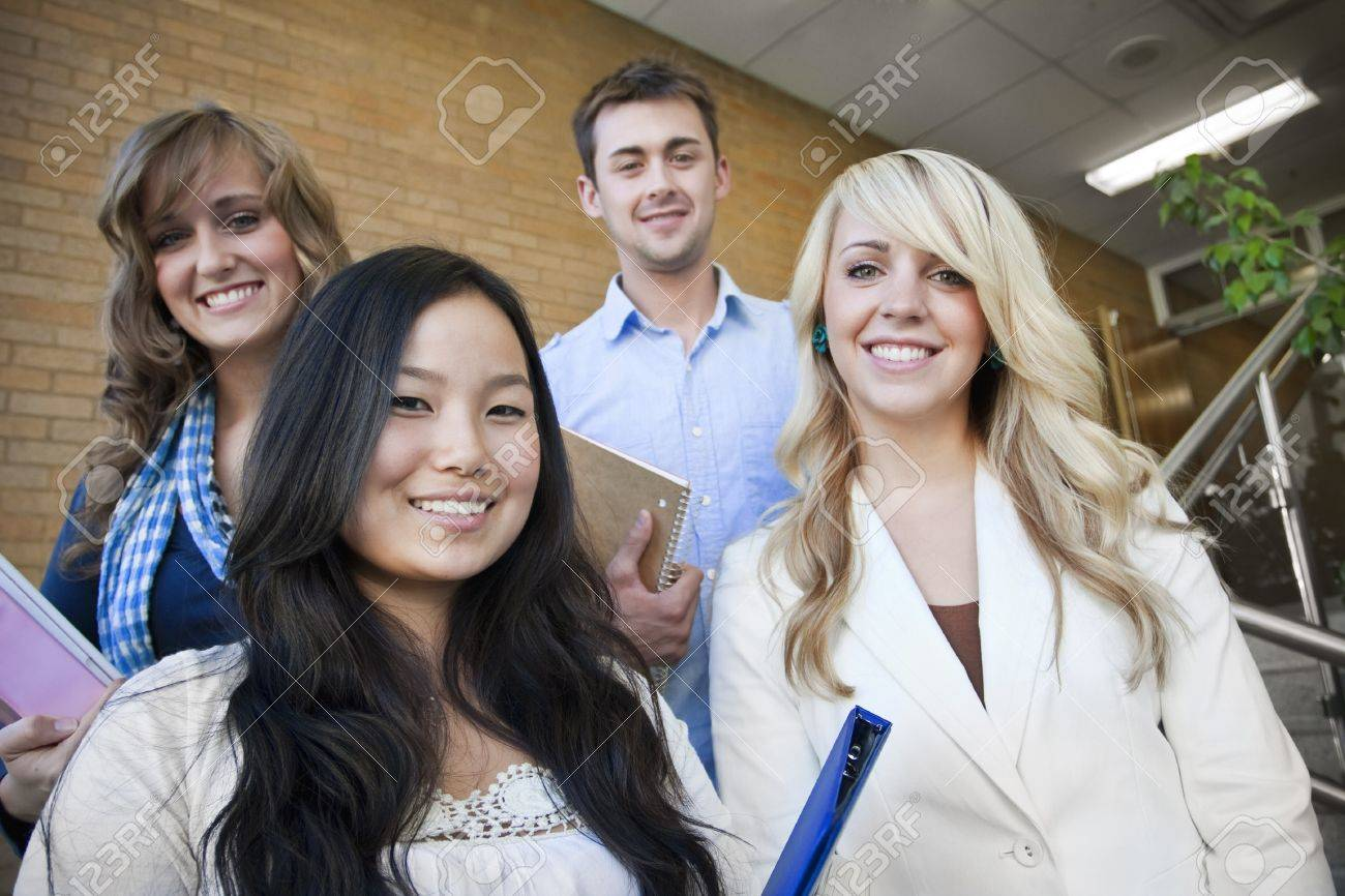 Four young, attractive students walking down the stairway at school Stock Photo - 9775114