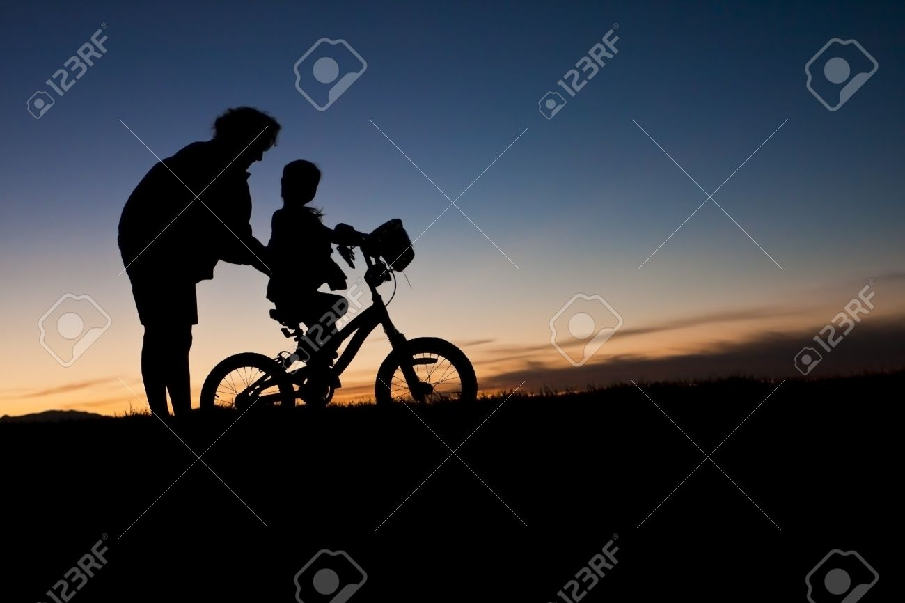 Parent helping a child Learn to Ride A bike Stock Photo - 8987703