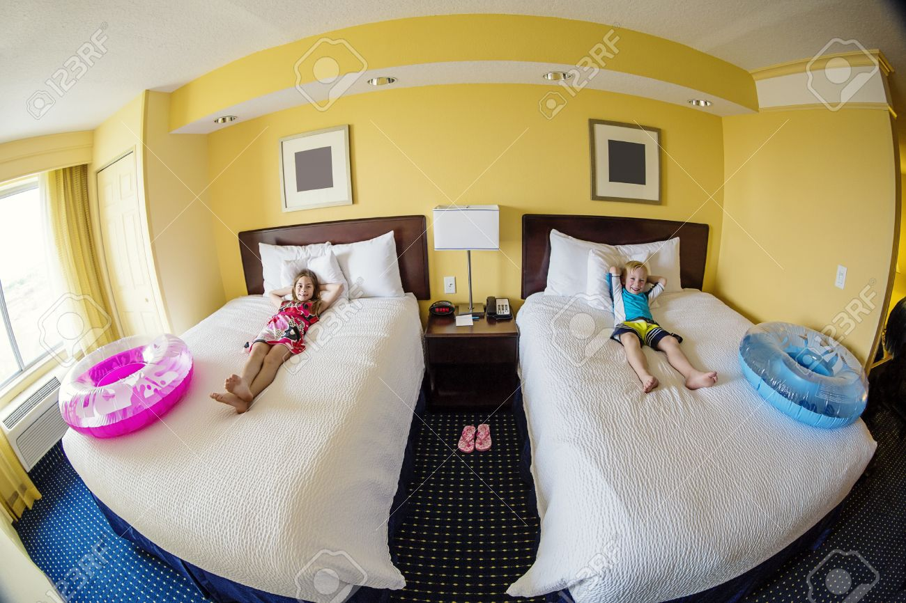 Cute Kids Laying On A Bed In A Hotel Room While On Fun Family Vacation Stock