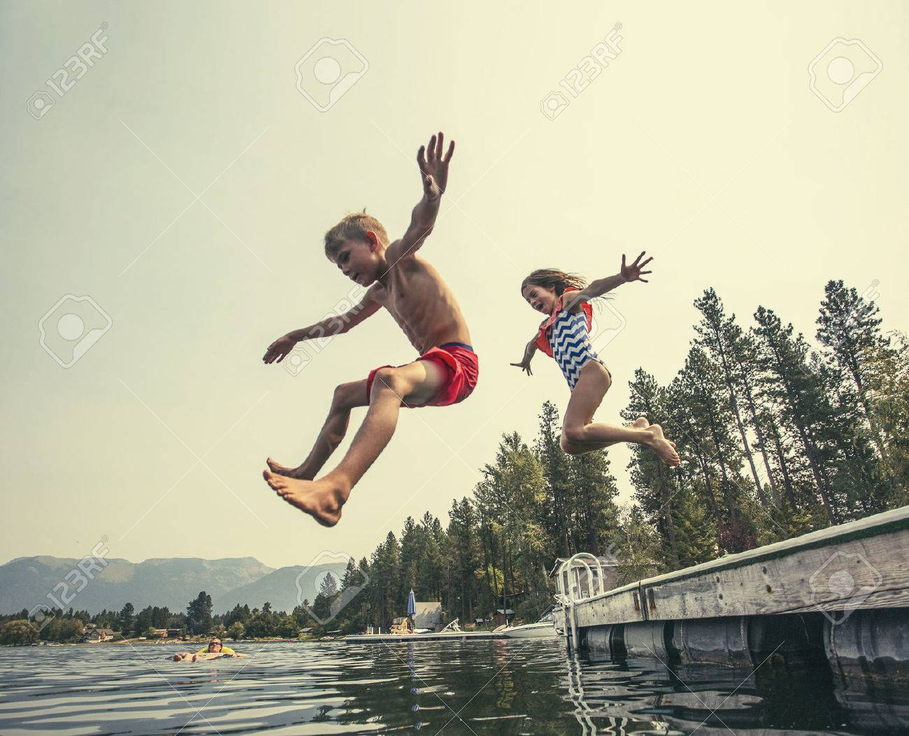Kids jumping off the dock into a beautiful mountain lake. Having fun on a summer vacation at the lake with friends - 54565686