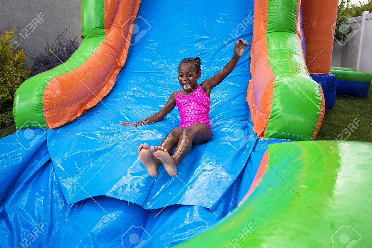 Happy little girl sliding down an inflatable bounce house - 54561867