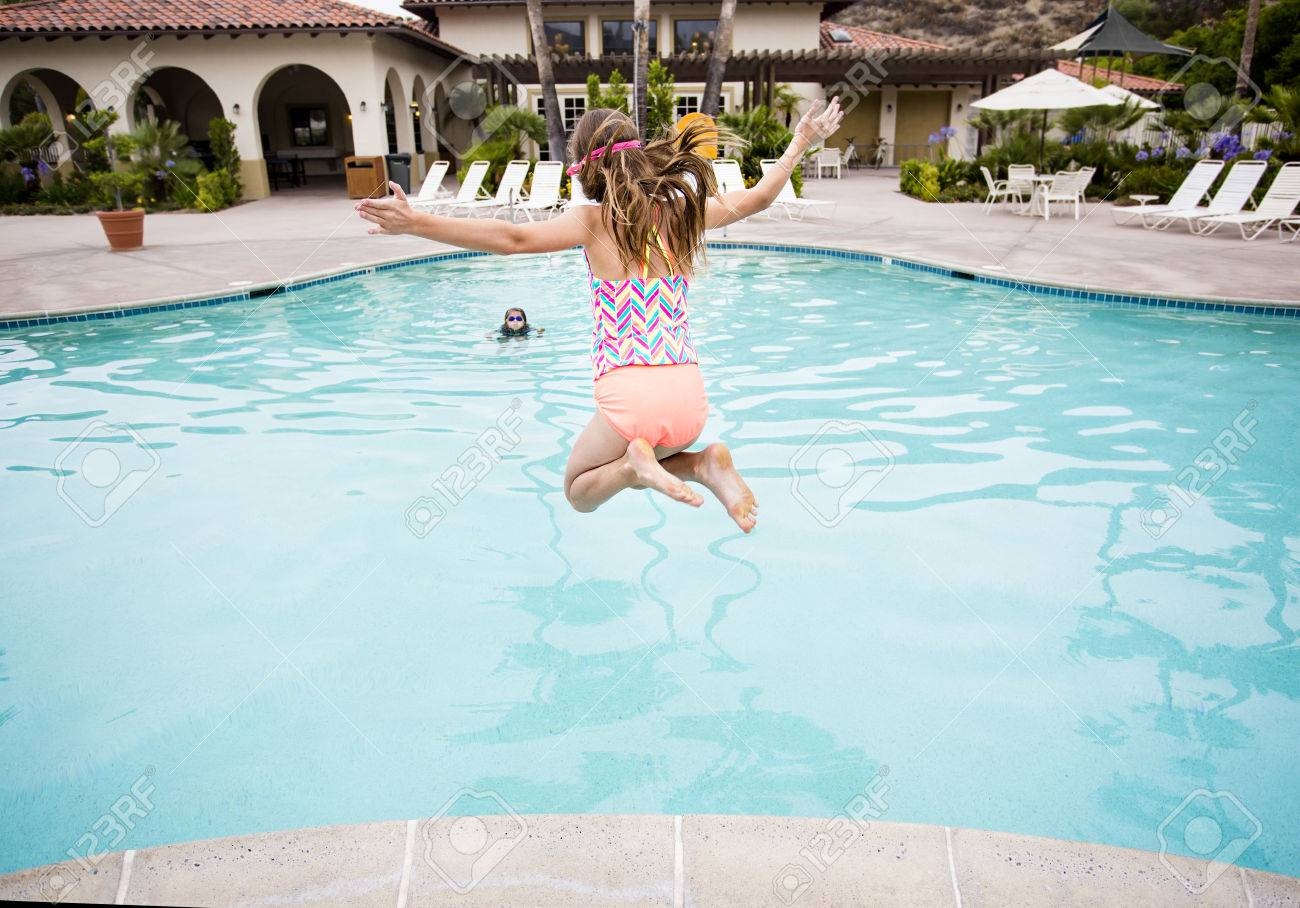 little jumping into a big backyard swimming pool view from