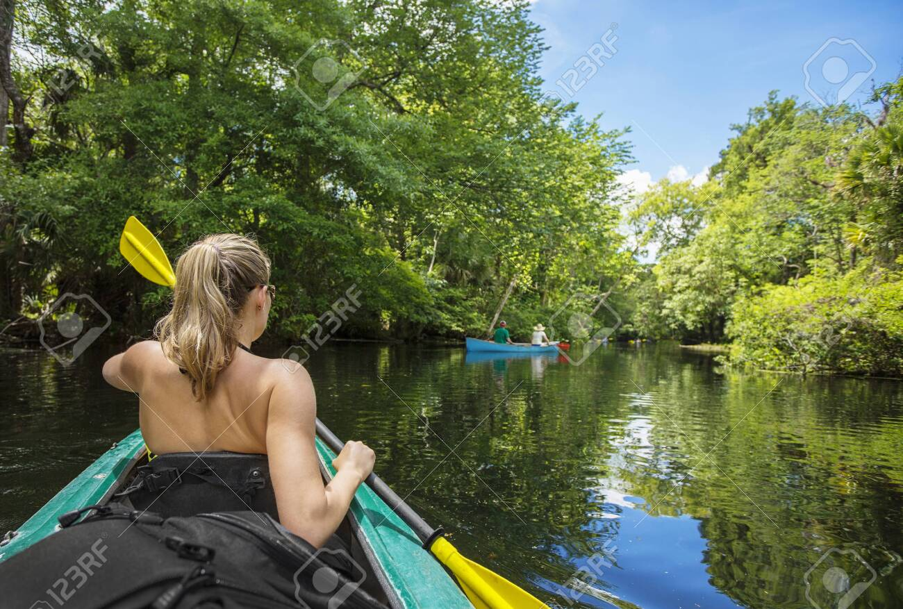 Adventuresome Woman kayaking along a beautiful tropical jungle river. Paddling along a calm beautiful river in a scenic natural backdrop - 142748814