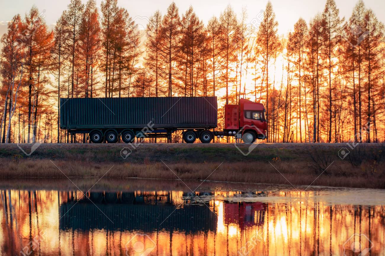 Red truck on a road at sunset. Focus on container - 110545629