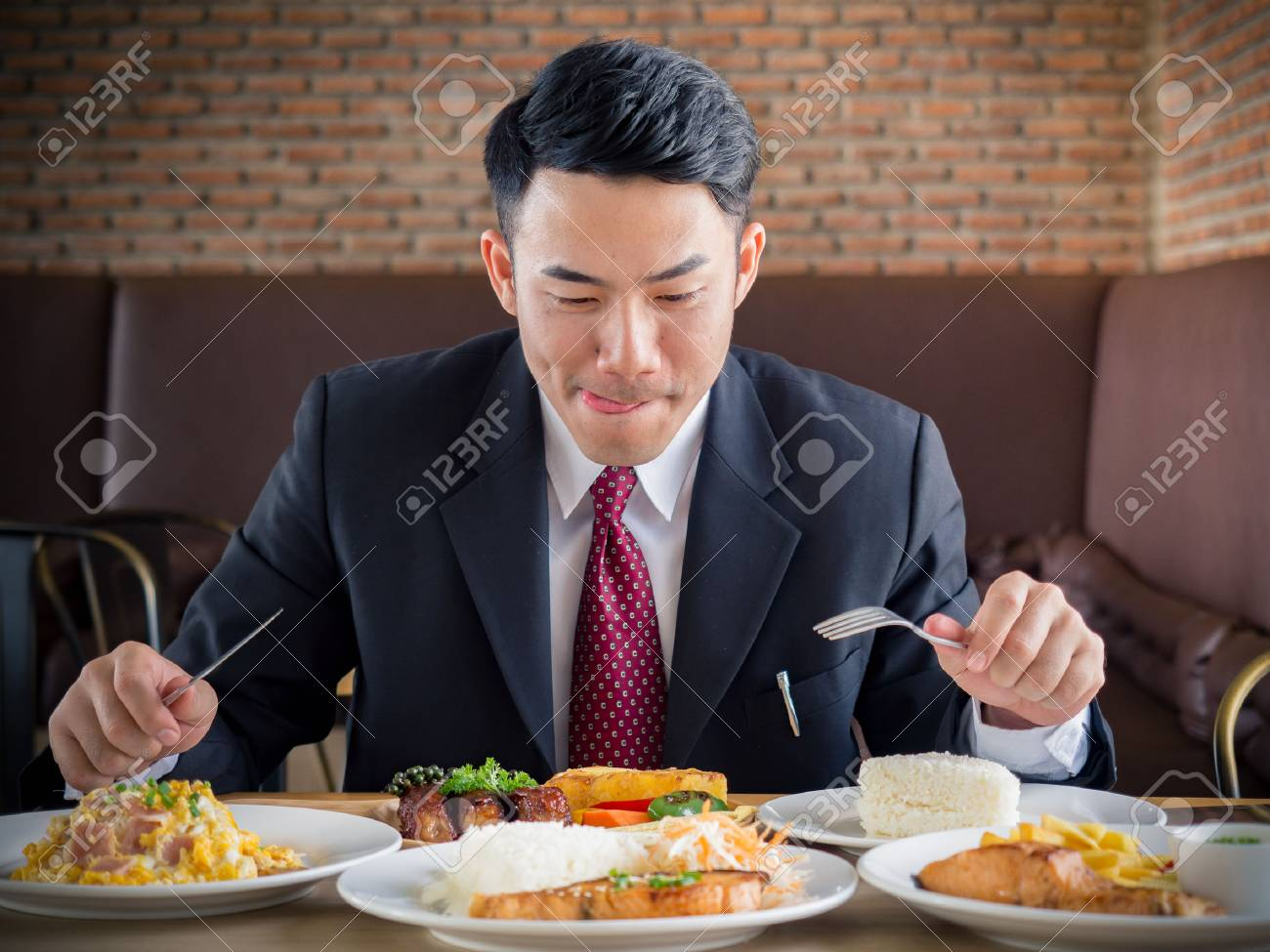Young asian businessman in formal suit feeling hungry, eating many foods on table at cafe - 87855726