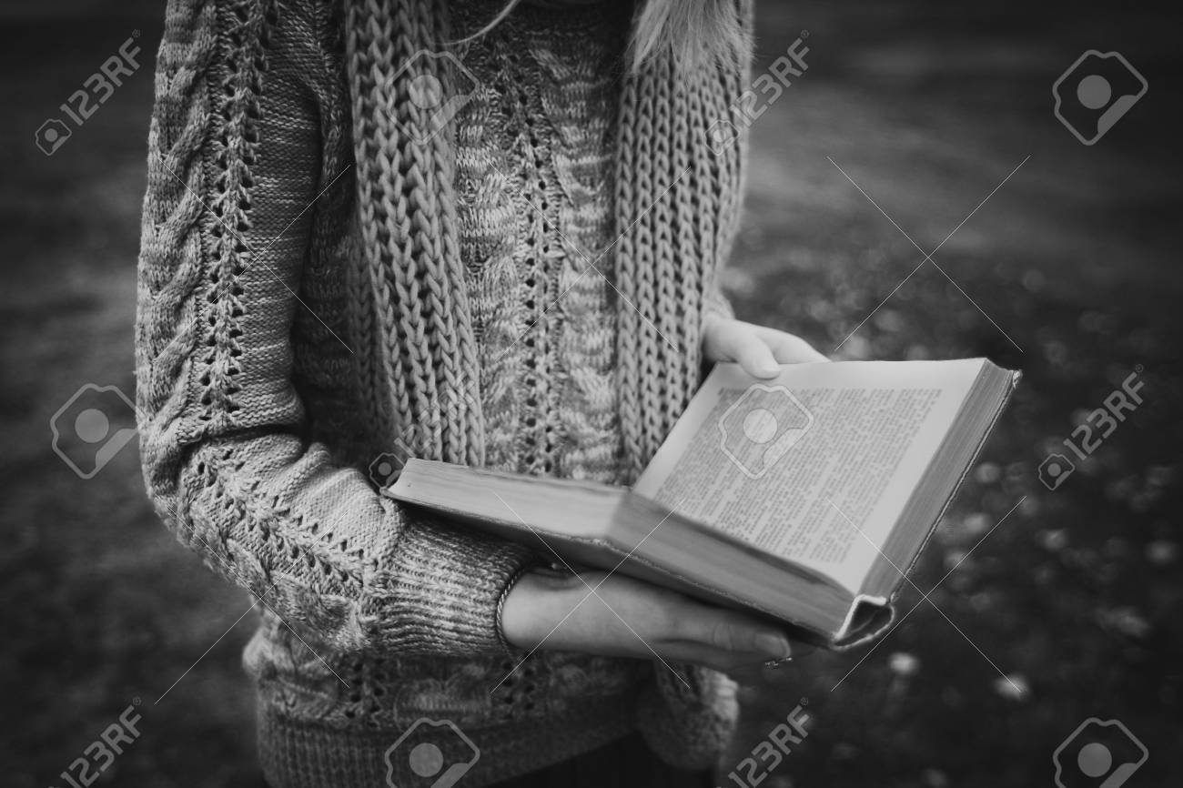 Black and white girls hands holding a paper book sad autumn mood stock photo
