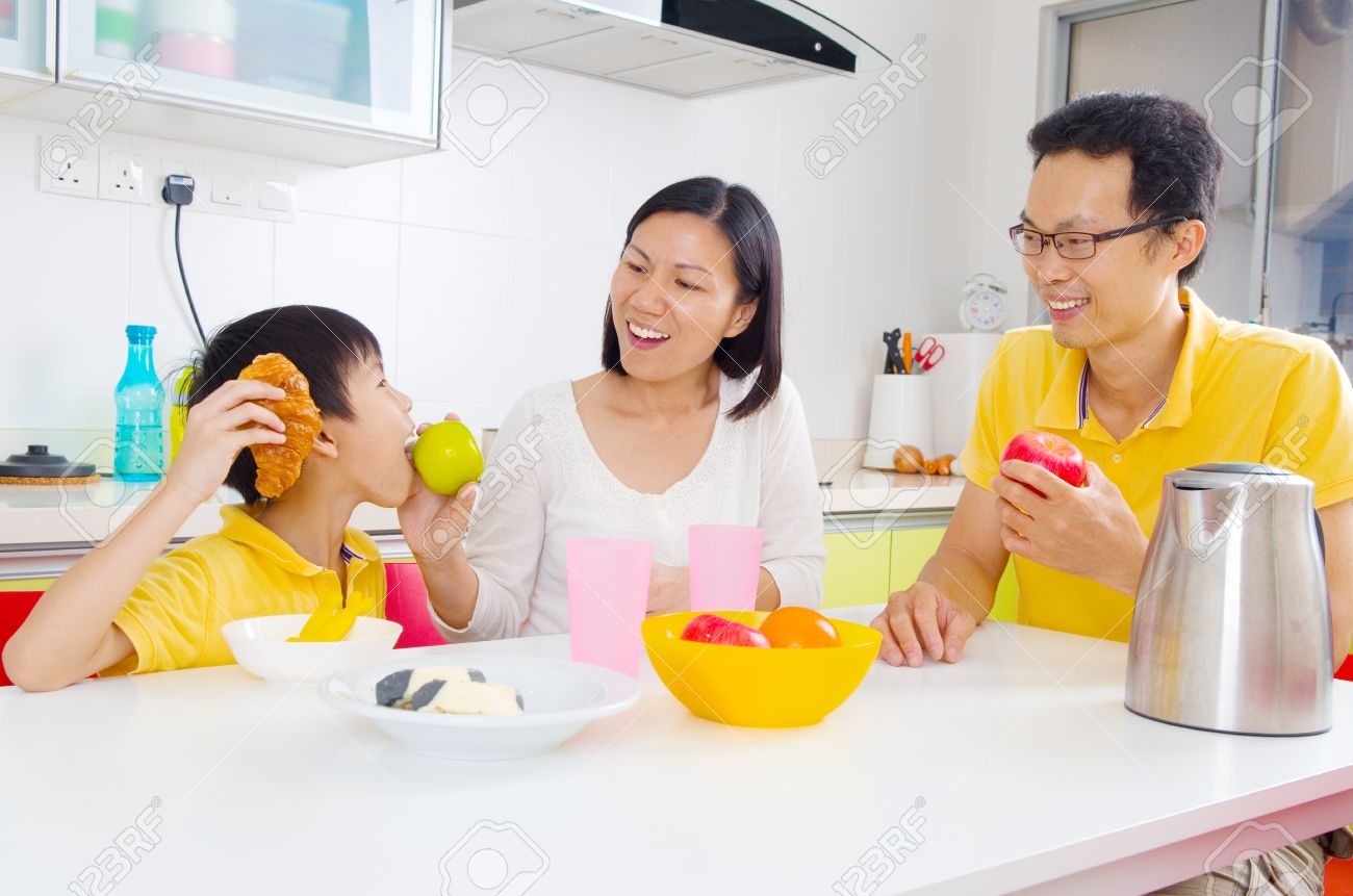 Happy family in kitchen - Happy Family And Son Eating Fruits In The Kitchen Stock Photo 41670933