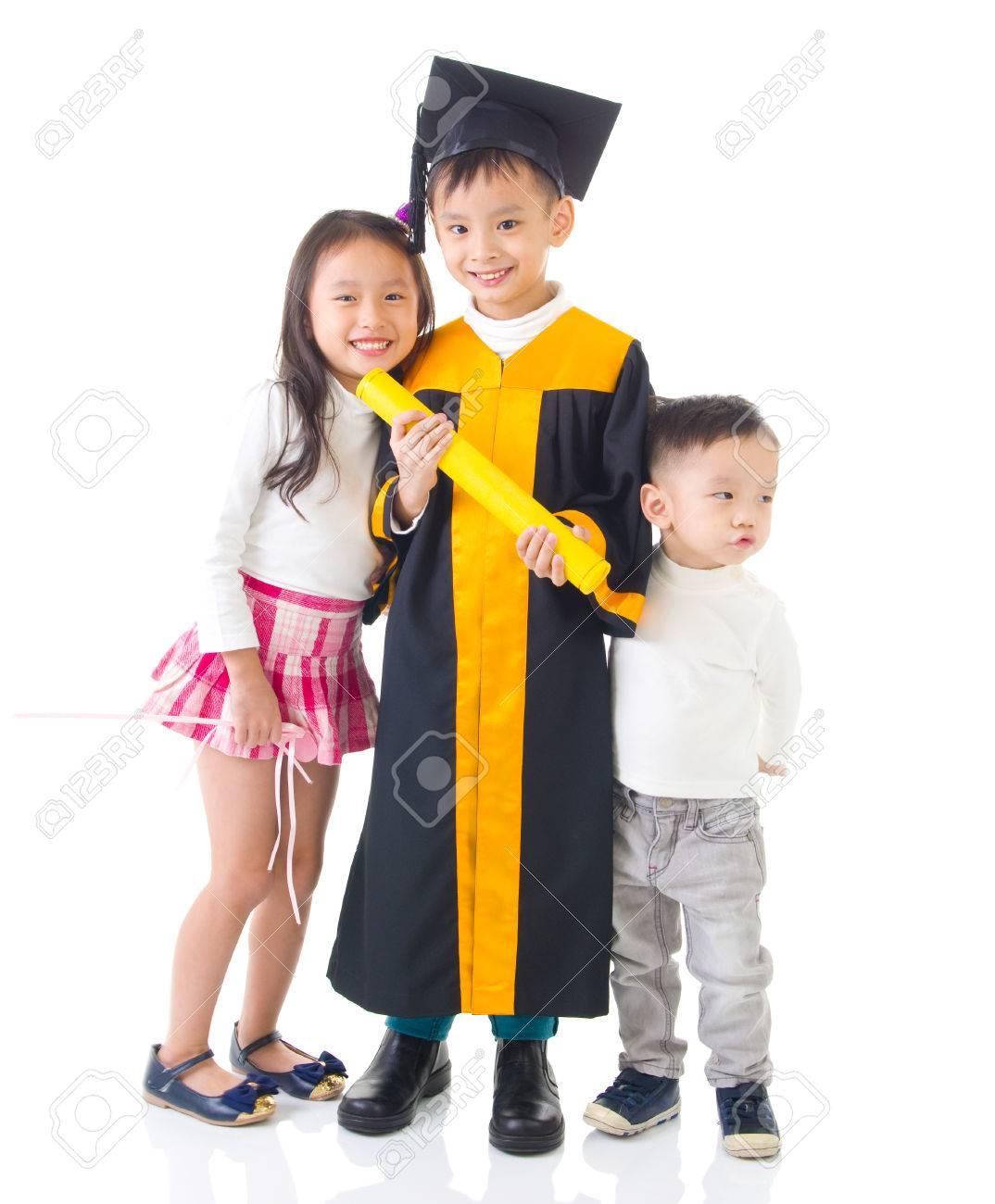 Asian School Kid Graduate In Graduation Gown And Cap. Taking.. Stock ...