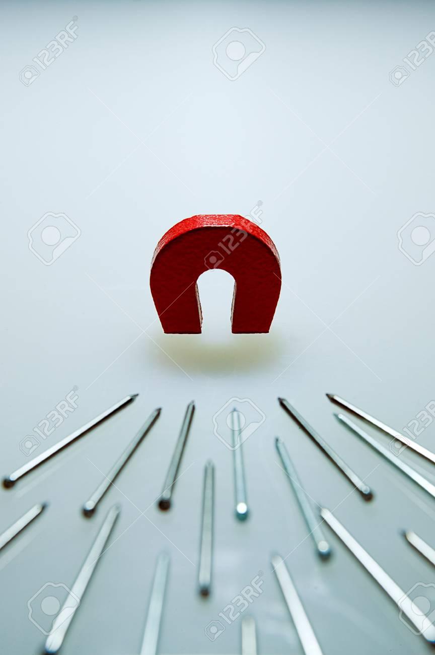 ein kleiner magnet mit einem stapel von stauchkopfnägel (brads