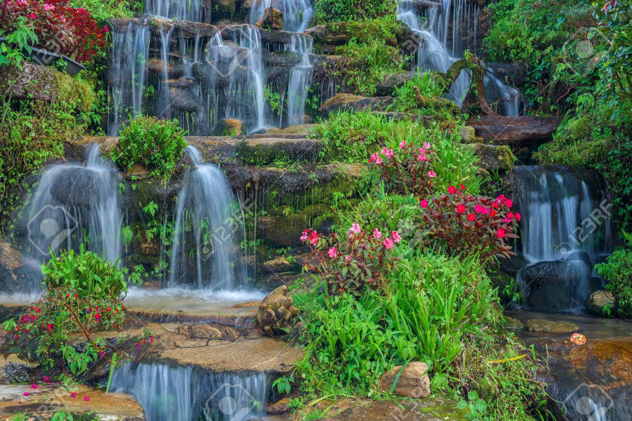 Beautiful Landscaping With Waterfall And Flowers Stock Photo
