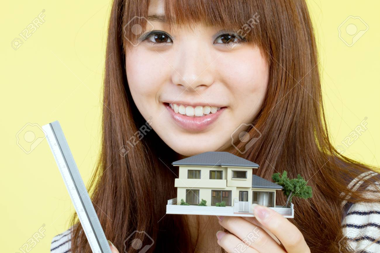 Beautiful young woman with house model Stock Photo - 11957275