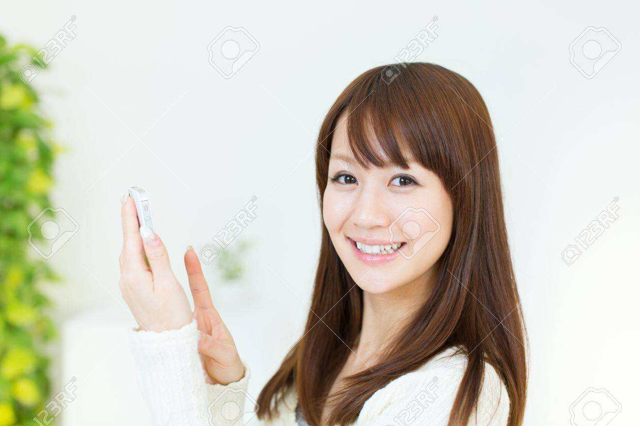 Beautiful young woman using a cellular phone Stock Photo - 17539916