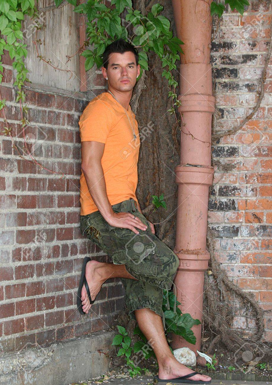 Young man posing on a brick wall in orange shirt Stock Photo - 6053911