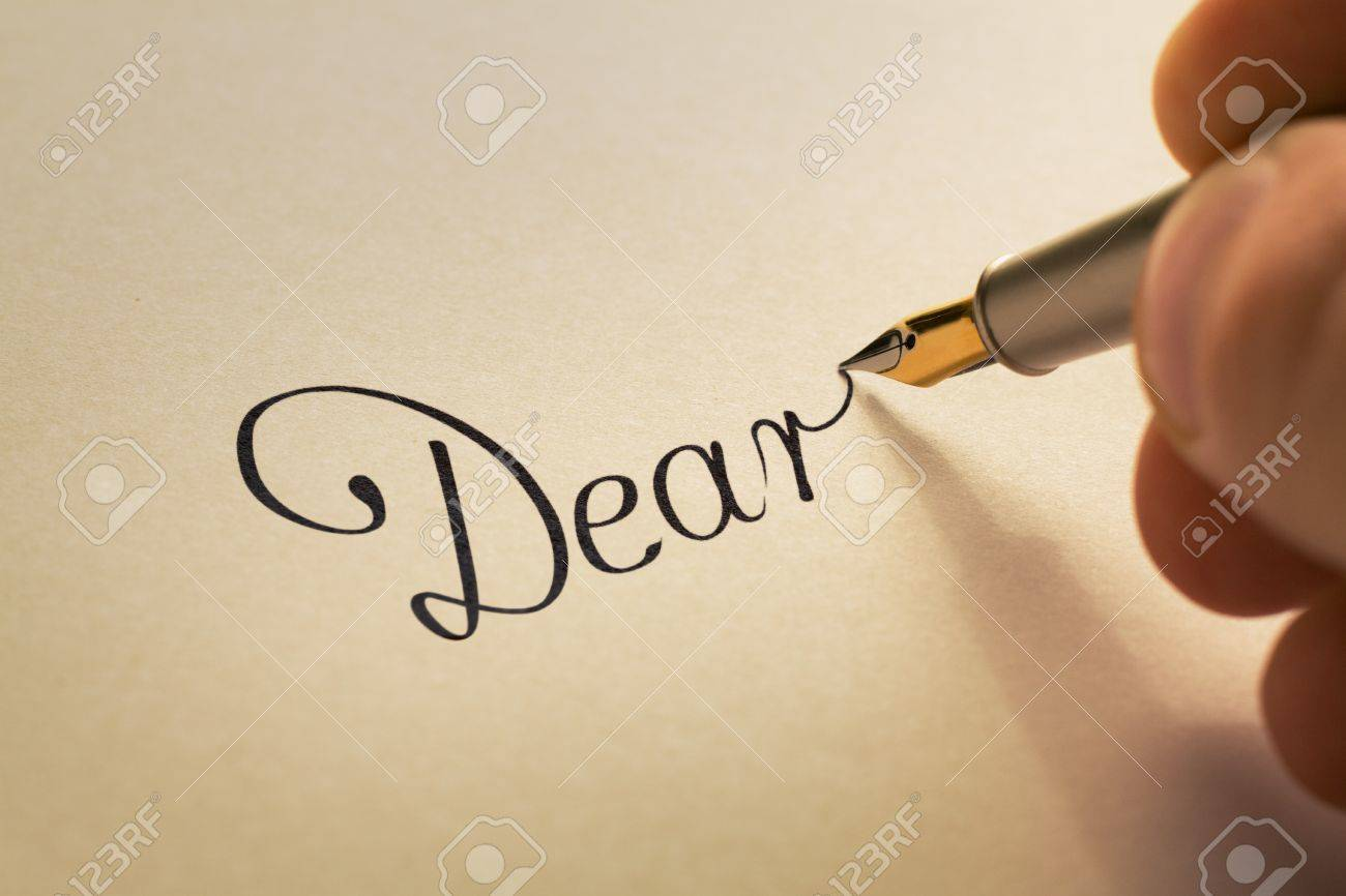Hand is writing calligraphic letter starting with dear using stock hand is writing calligraphic letter starting with dear using old pen on yellow paper stock photo spiritdancerdesigns Gallery